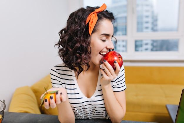 Retrato alegre mujer joven emocionada con pelo rizado disfrutando de manzana roja en apartamento moderno. sonreír, divertirse, relajarse en casa, comodidad, relajarse, felicidad