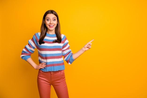 Retrato de alegre niña confiada señalando consejos de espacio de copia