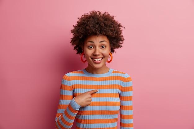 El retrato de una alegre niña de pelo rizado sonríe positivamente, se le pide que participe, alguien se menciona a sí misma, fue elegida o promovida, usa un suéter a rayas, aislado en una pared rosa