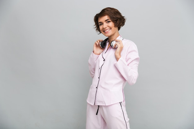 Retrato de una alegre niña sonriente en pijama con auriculares