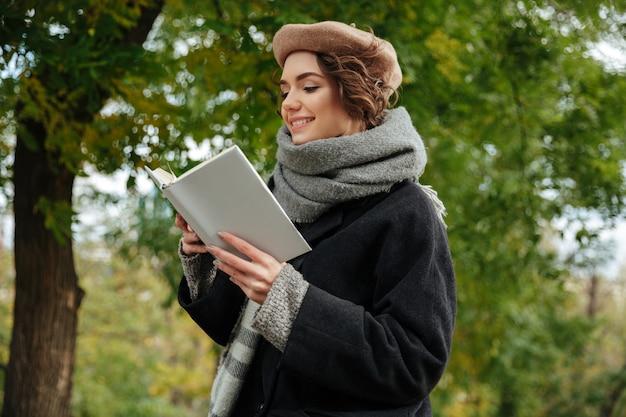 Retrato de una alegre niña vestida con ropa de otoño leyendo