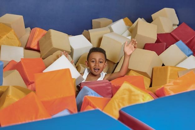 Retrato de alegre niño afroamericano enérgico divirtiéndose en el parque de trampolines durante el fin de semana