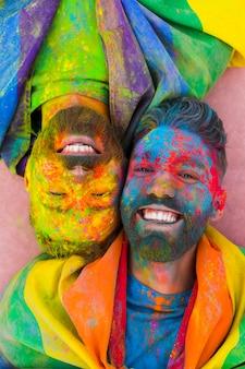 Retrato de alegre pareja gay enamorada manchada en pintura