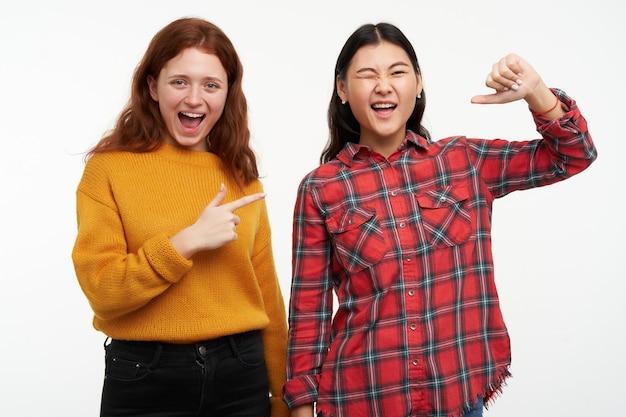 Retrato de alegres amigos asiáticos y caucásicos. vistiendo ropa casual. niña feliz apuntando a su amiga que le guiña un ojo y apuntando a sí misma. aislado sobre pared blanca