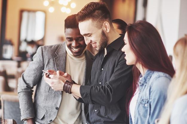 Retrato de alegres jóvenes amigos mirando el teléfono inteligente mientras está sentado en la cafetería