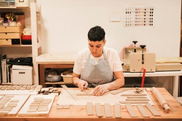 Retrato de alfarero femenino cortando la arcilla en forma rectangular en mesa de madera