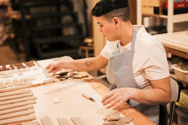 Retrato de un alfarero que arregla los azulejos de arcilla en la mesa de madera en el taller