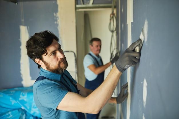 Retrato de alto ángulo de dos trabajadores de la construcción construyendo drywall mientras se renueva la casa, espacio de copia