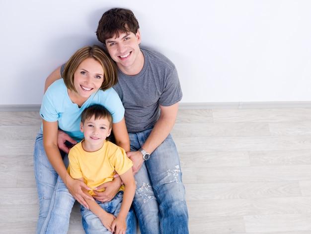 Retrato de alto ángulo de familia joven feliz con niño sentado en el suelo en casuals