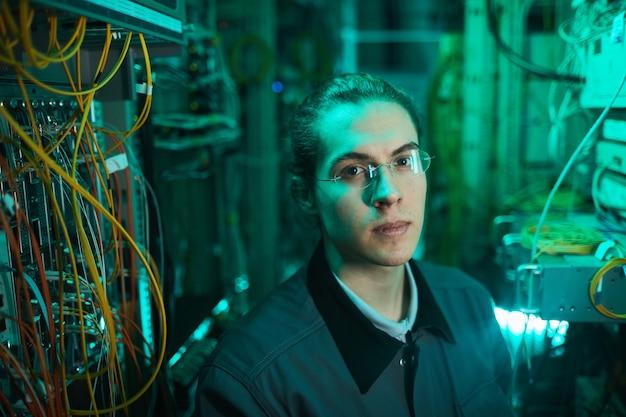 Retrato de alto ángulo de joven técnico de red mirando a la cámara en la sala de servidores mientras configura la supercomputadora en el centro de datos, espacio de copia