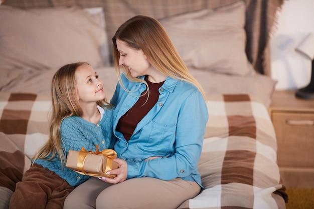 Retrato de alto ángulo de madre feliz abrazando a linda chica y sonriendo el uno al otro mientras abre el presente sentado en la cama, espacio de copia