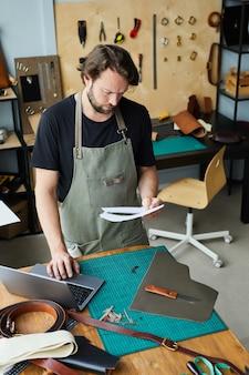 Retrato de alto ángulo vertical de artesano masculino moderno usando laptop mientras trabajaba en el taller de curtidores