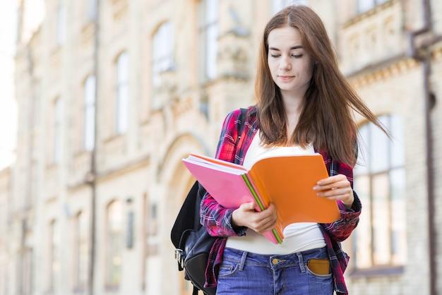 Retrato de alumna con libro en ciudad