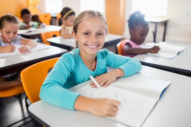 Retrato de alumno sonriente sentado en el escritorio