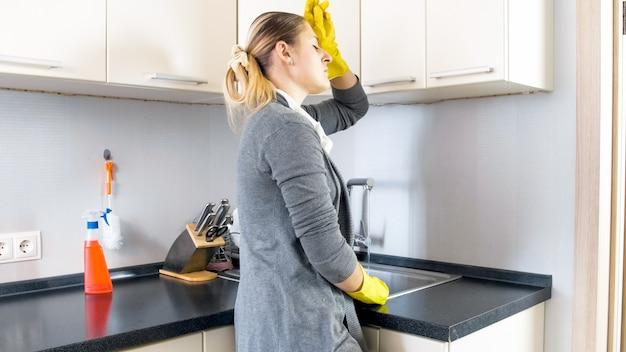 Retrato de ama de casa cansada y estresada de pie en la cocina.