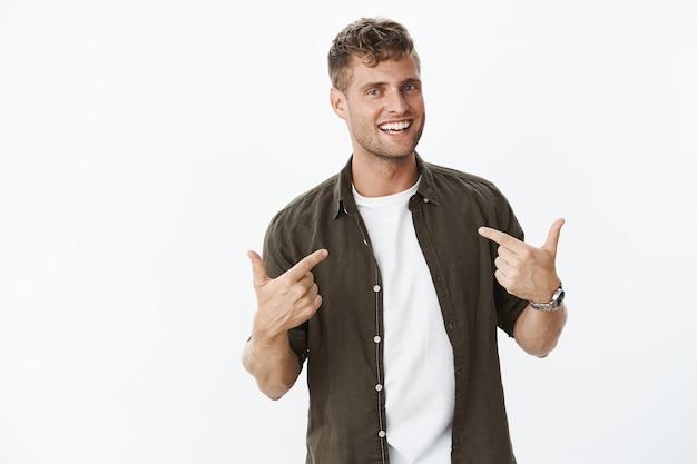 Retrato de amable carismático, autosatisfecho y orgulloso, rubio, masculino, apuntando a sí mismo, indicando el cuerpo y sonriendo ampliamente como queriendo ser elegido sobre la pared gris