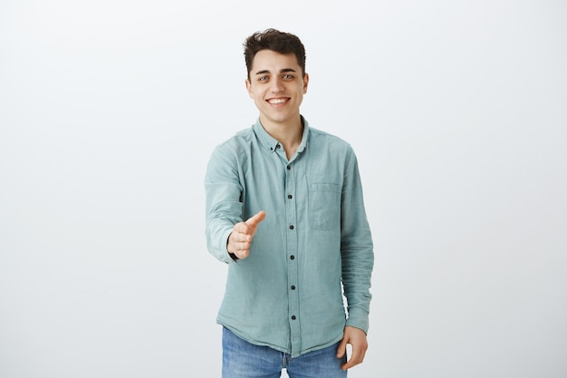 Retrato de amable hombre europeo saliente en camisa de moda casual