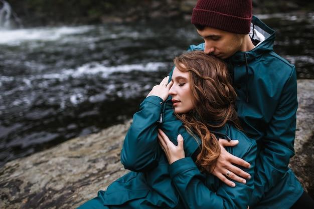 Retrato de amantes en impermeables verdes, sentados en una piedra, contra una cascada
