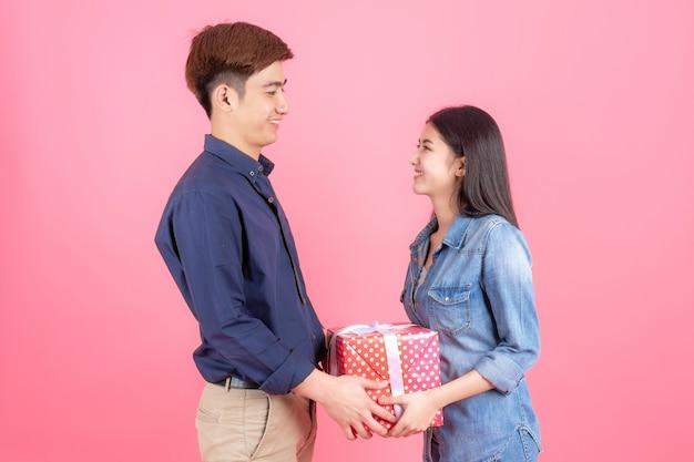 Retrato amigable hombre y mujer adolescentes, están colocados en una caja de regalo roja y sonriendo con un divertido concepto de pareja asiática adolescente