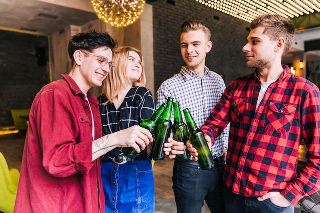 Retrato de un amigo tostado de las botellas de cerveza verde en el restaurante pub