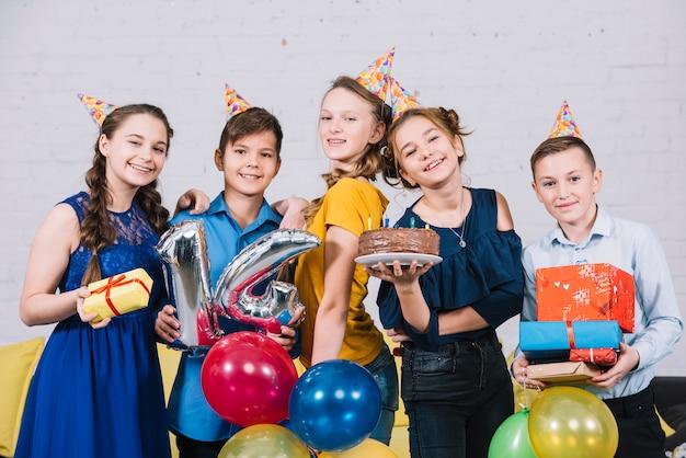 Retrato de amigos adolescentes felices disfrutando el cumpleaños sosteniendo un pastel de cumpleaños; regalos y número 14 de globo de aluminio.