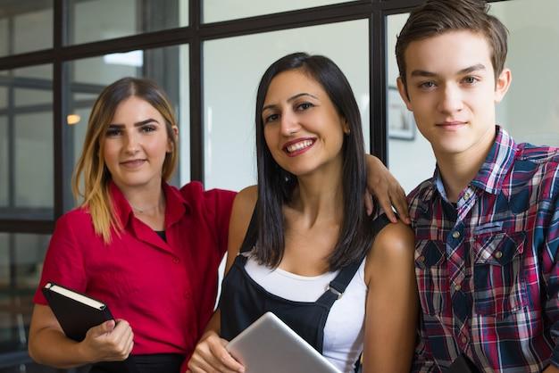 Retrato de amigos felices jóvenes estudiantes abrazándose y sonriendo