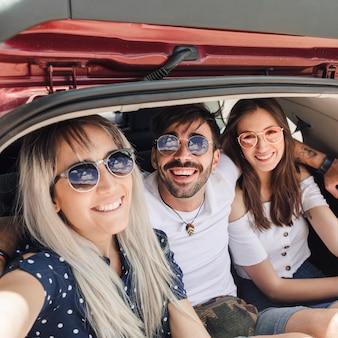 Retrato de amigos felices que se sientan dentro del tronco del coche