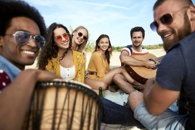 Retrato de amigos felices sentados en la playa con instrumentos musicales