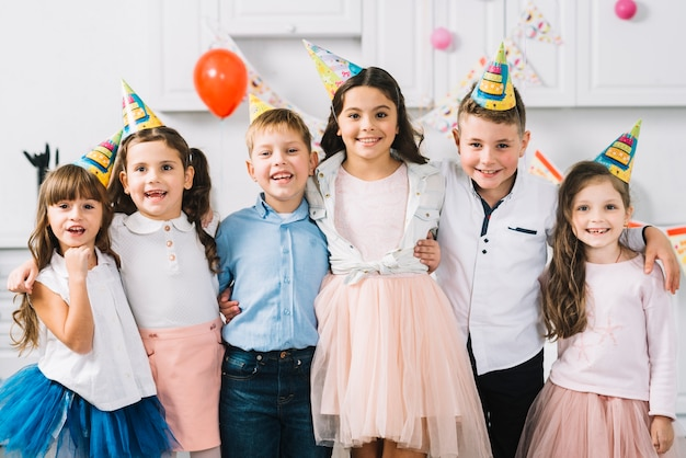 Retrato de amigos felices vistiendo sombrero de fiesta de pie juntos
