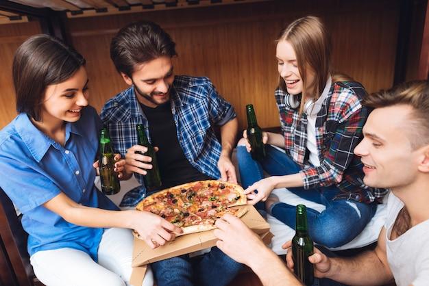 Retrato de amigos que se relajan juntos, comen pizza