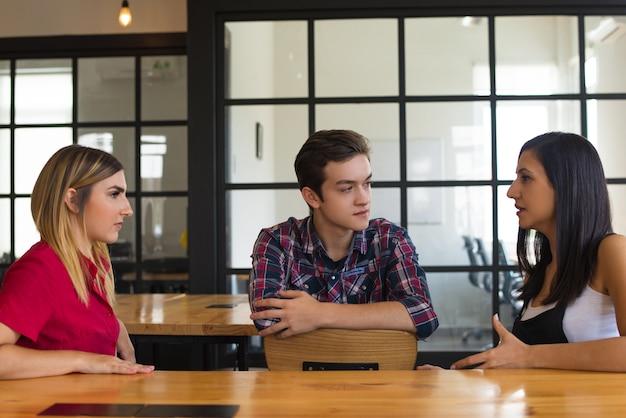 Retrato de amigos serios estudiantes sentados en la mesa y hablando