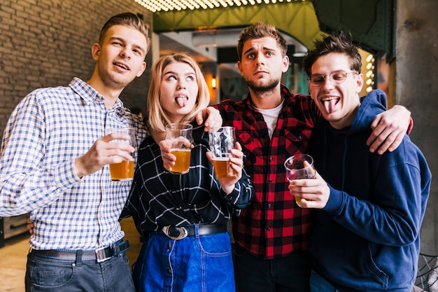 Retrato de amigos sosteniendo los vasos de cerveza