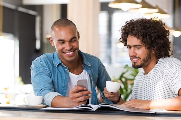 Retrato de amigos viendo videos en el teléfono mientras toma un café en la cafetería