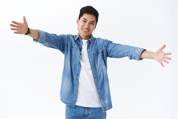 Retrato de un amistoso carismático joven apuesto taiwanés que te alcanza para un cálido abrazo, estira las manos hacia los lados sonriendo, invita a dar una cálida bienvenida, abrazos, de pie en la pared blanca