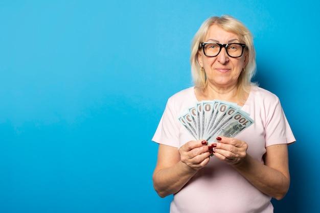 Retrato de una anciana amigable en camiseta casual y gafas con dinero en sus manos en una pared azul aislada. cara emocional concepto riqueza, victoria, crédito, pensión