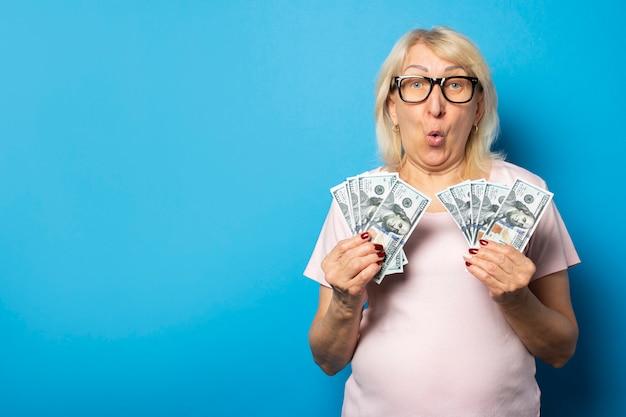 Retrato de una anciana amigable con una cara sorprendida en una camiseta casual y gafas con dinero en sus manos en una pared azul aislada. cara emocional concepto riqueza, ganar, préstamo, pensión