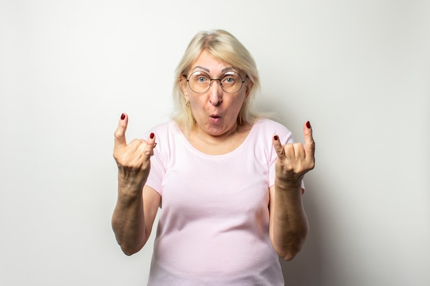 Retrato de una anciana amigable con una cara sorprendida en una camiseta casual y gafas hace un gesto de rock and roll, cabra en una pared de luz aislada. cara emocional fiesta de gestos