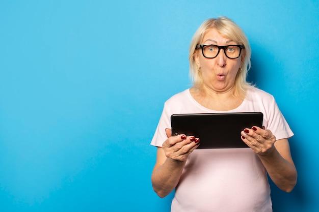 Retrato de una anciana amigable con una cara sorprendida en gafas y una camiseta casual con una tableta en sus manos en una pared azul aislada. cara emocional