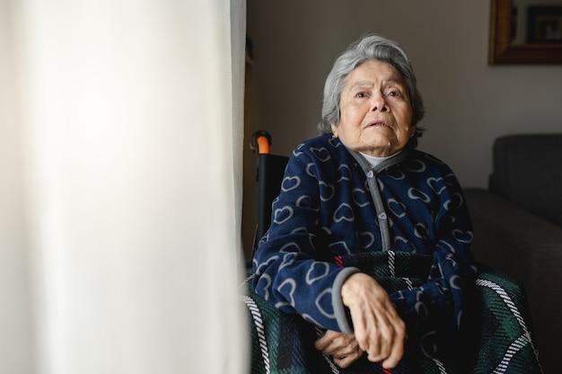 Retrato anciana enferma sentada en silla de ruedas en casa con cara desorientada y confundida .. tercera edad, concepto de asistencia a ancianos en el hogar.