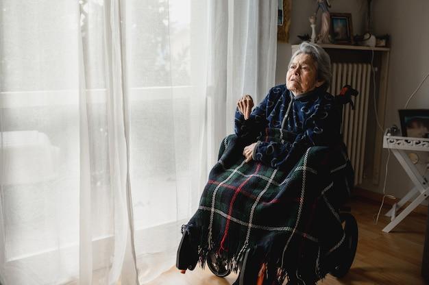 Retrato anciana enferma sentada en silla de ruedas en casa. tercera edad, concepto de asistencia domiciliaria para ancianos.