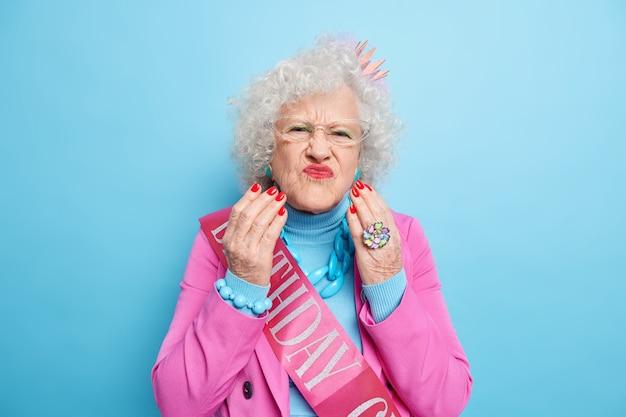 Retrato de anciana con estilo con el pelo gris y rizado pucheros labios pintados de rojo hace griace infeliz viste ropa de moda y una pequeña corona en la cabeza celebra birhday quiere ser siempre joven