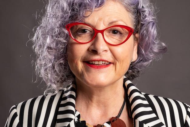 Retrato de anciana sonriente con anteojos rojos