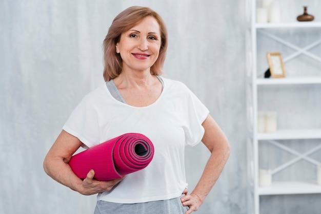 Retrato de una anciana sonriente sosteniendo la estera de yoga enrollada