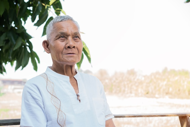 Retrato de anciano asiático está sonriendo mirando hacia adelante