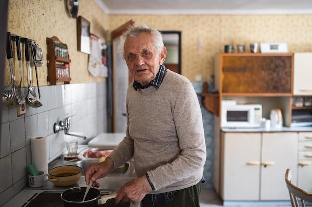 Retrato de anciano cocinando en la estufa en el interior de su casa, revolviendo y mirando a la cámara.