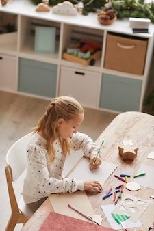 Retrato de ángulo alto vertical de una adolescente rubia haciendo los deberes mientras está sentado en el escritorio en el interior de una casa, espacio de copia