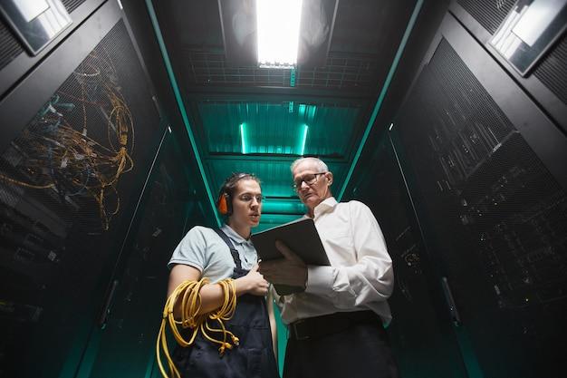 Retrato de ángulo bajo de dos ingenieros con tableta en la sala de servidores mientras realiza trabajos de mantenimiento en el centro de datos, espacio de copia