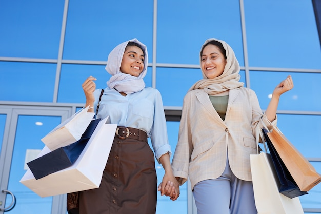 Retrato de ángulo bajo de dos jóvenes mujeres de oriente medio sosteniendo bolsas de compras y sonriendo el uno al otro mientras salen del centro comercial con compras
