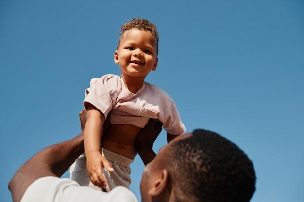 Retrato de ángulo bajo de feliz padre afroamericano jugando con lindo bebé y tirándolo contra b ...