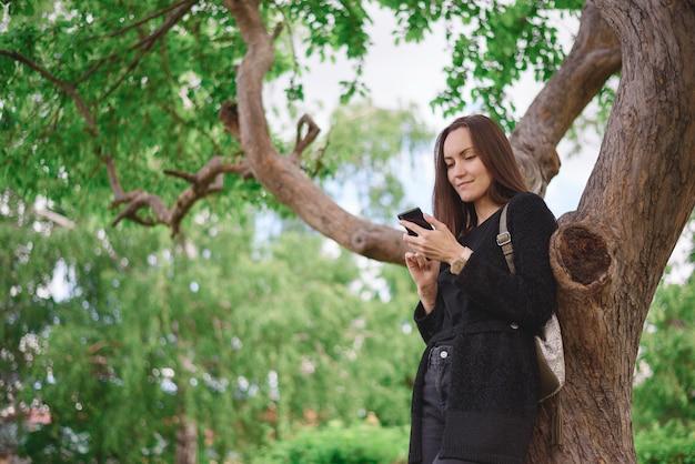 Retrato desde el ángulo inferior de una mujer joven en una chaqueta negra con un teléfono inteligente en sus manos en el fondo de un gran árbol ramificado. comunicación virtual, generación z